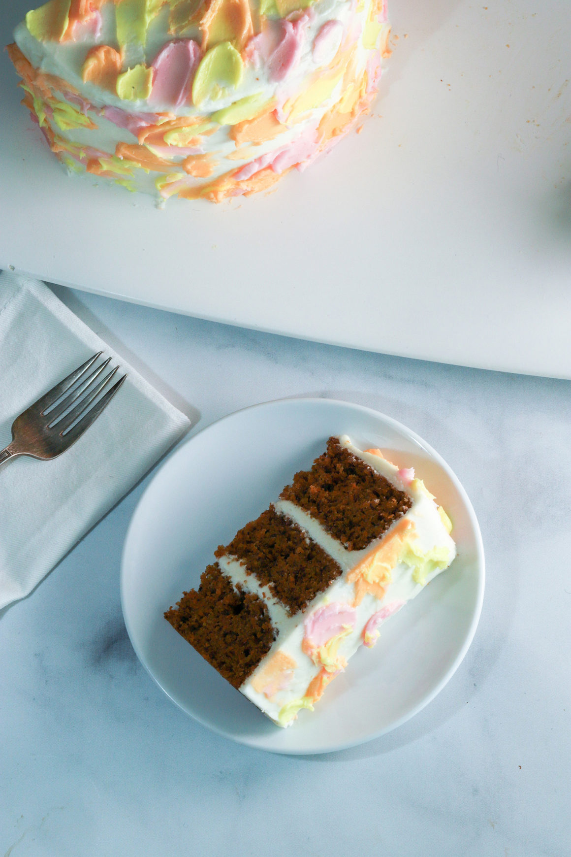 carrot cake slice with pastel colored frosting