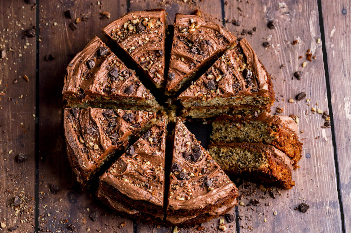 banana cake with chocolate frosting and toasted pecans