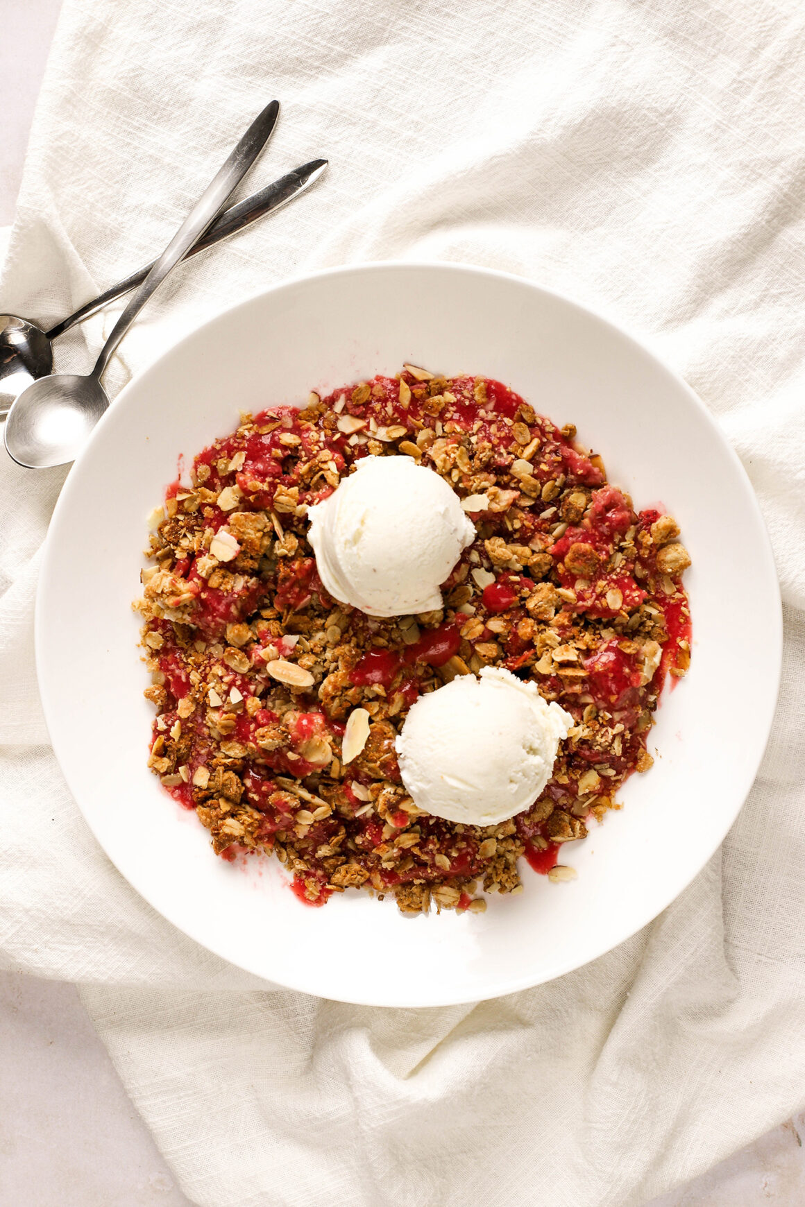 strawberry crisp in low bowl with vanilla bean ice cream
